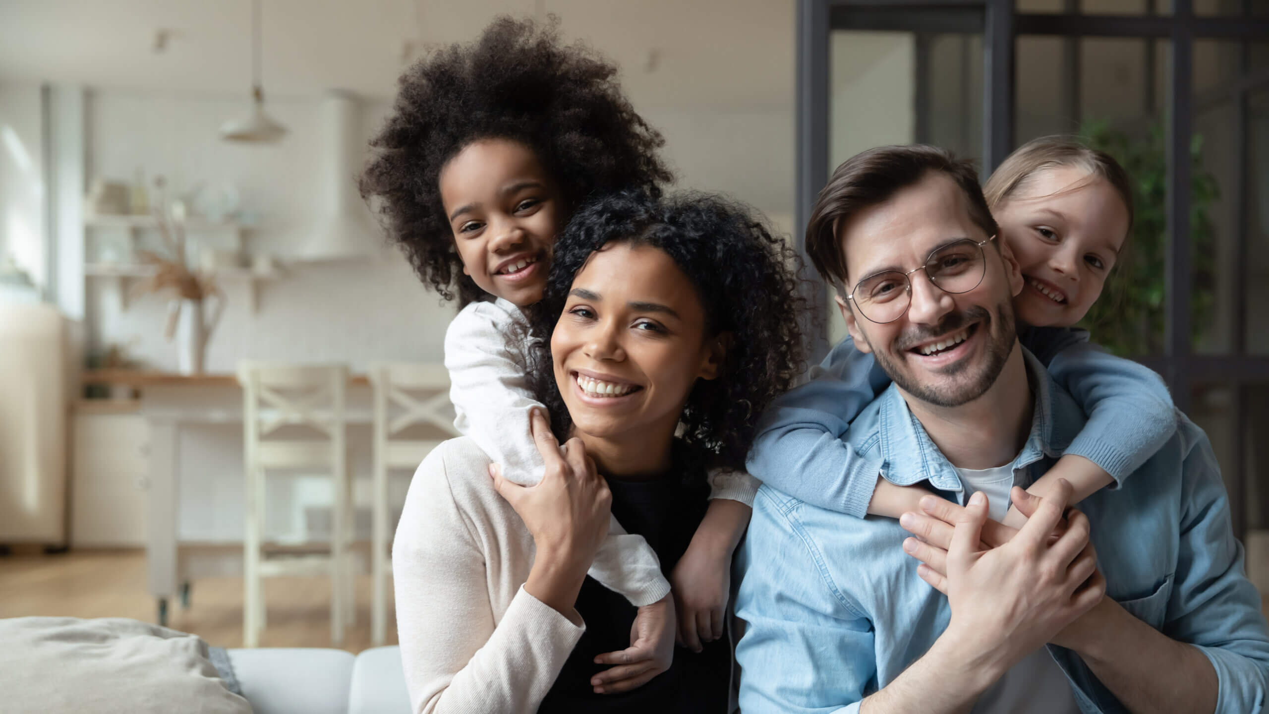 Portrait of happy multiracial couple enjoying sweet family moment with adorable little mixed raced daughters at home. Smiling cute small stepsisters cuddling cheerful parents, looking at camera.
